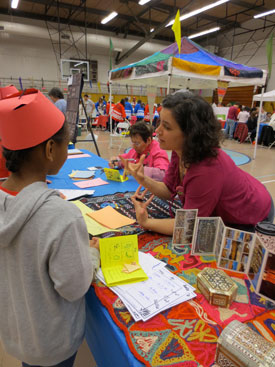 Dena El Safaar (right) of the Bloomington Arab American Association talks to a Monroe County 4th-grader at the 2014 Lotus Blossoms World Bazaar.